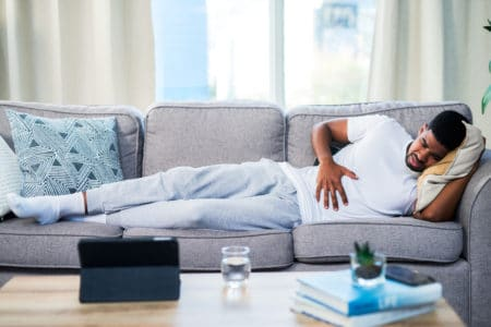 Man laying down holding stomach - food poisoning treatment